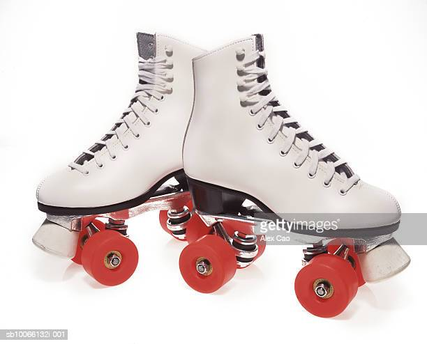 pair of roller-skates on white background - roller skating stock photos and pictures