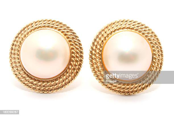 Pair of round pearl earrings on white background