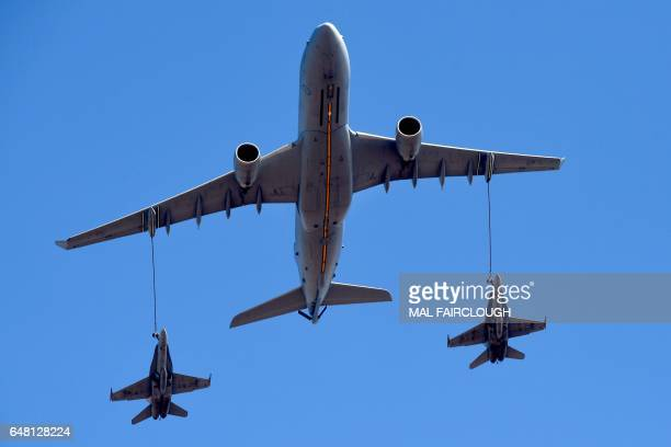 A pair of Royal Australian Air Force F/A18 Hornet aircraft fly in midair refueling formation with an Airbus A330 MRTT multirole tanker aircraft...