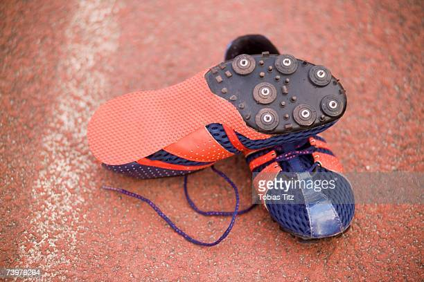 pair of running spikes on a running track - cleats stock pictures, royalty-free photos & images