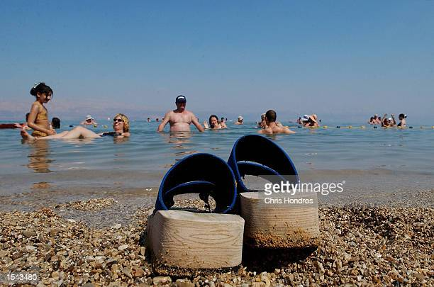 A pair of sandals sit on the rocky beach while people soak in the water May 17 2002 at the Dead Sea in the West Bank Tourism is sharply down in...