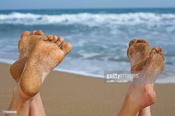 Pair of sandy feet on beach.