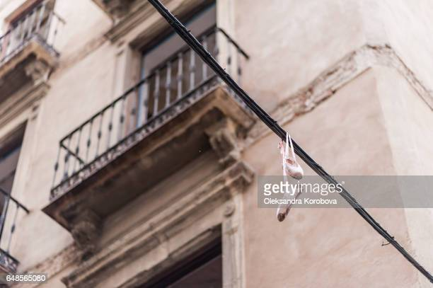 Pair of satin silk ballet slippers hag above the medieval streets, balconies in the background. Artistic composition.