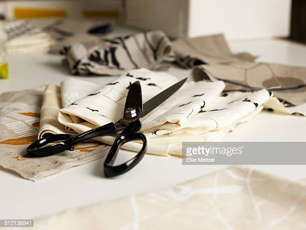 Pair of scissors and fabric on work table
