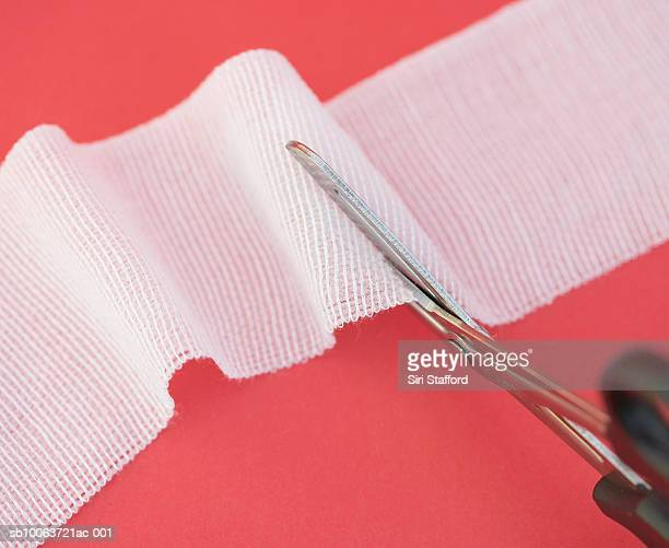 pair of scissors cutting into strip of gauze, close-up - gauze stock pictures, royalty-free photos & images
