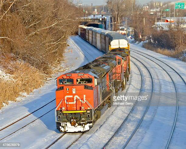 Pair of SD70M-2's and a pair of zebra striped geeps lead 401 westward into the strong but soon to set sun in Montreal West.