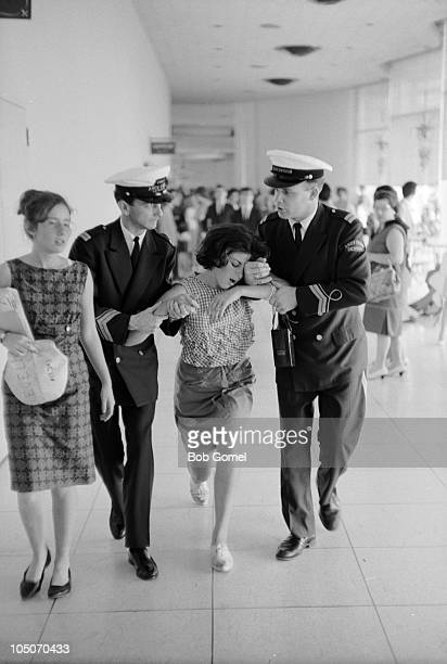 A pair of security guards half carry and half walk a woozy young woman along a corridor in the Deauville Hotel after she saw the Beatles Miami Beach...