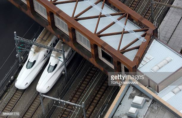 A pair of Shinkansen trains are seen under a pedestrian overbridge in Tokyo on August 15 2016 Japan's economy stalled in the AprilJune quarter data...