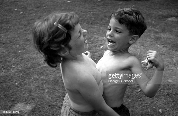 A pair of shirtless children a girl and a boy play outdoors New Jersey 1950s