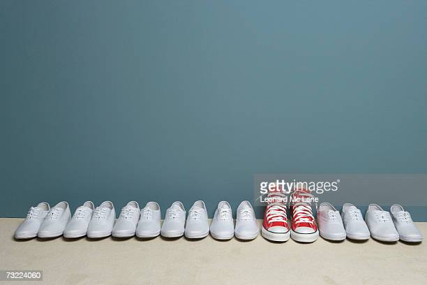 pair of shoes in row against wall - group of objects stock photos and pictures