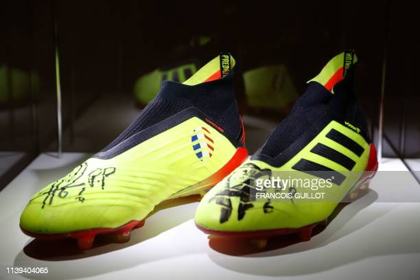A pair of shoes worn by French midfielder Paul Pogba on July 15 2018 during the World Cup 2018 final match is displayed at Christies auction house on...