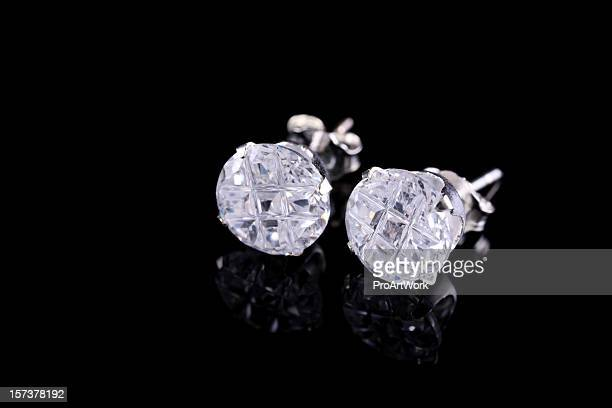 Pair of silver diamond stud earrings on a black background