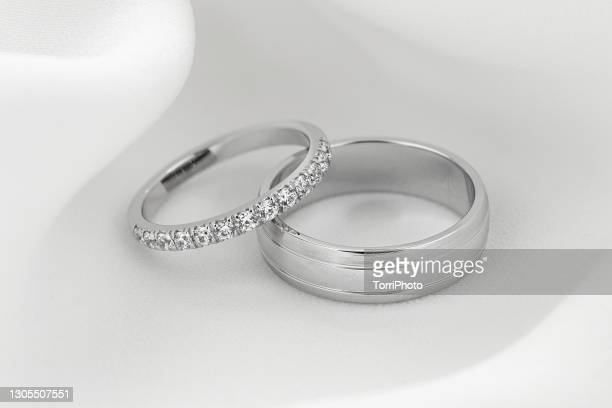 pair of silver wedding rings. female ring with diamonds - white gold stock pictures, royalty-free photos & images