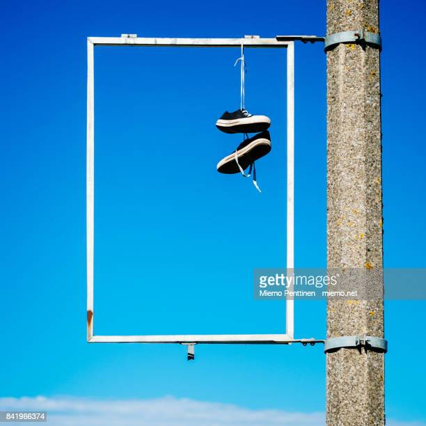 A pair of sneakers hanging inside an empty advertisement frame against blue sky