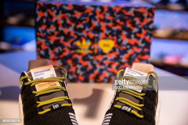 A pair of sneakers with a public transport ticket is on display as people queue up to buy the Adidas / BVG trainers outside the Overkill shoe store...