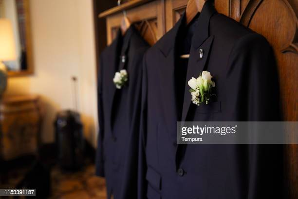pair of suits hanging ready for the wedding. - civil partnership stock pictures, royalty-free photos & images
