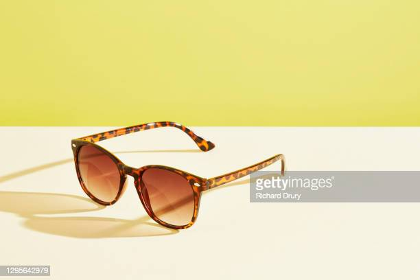 a pair of sunglasses against a yellow background - richard drury stock pictures, royalty-free photos & images