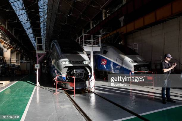 Pair of TGV high-speed railway train stand inside a hangar inside the Alstom SA factory in Belfort, France, on Thursday, Oct. 26, 2017. The creation...