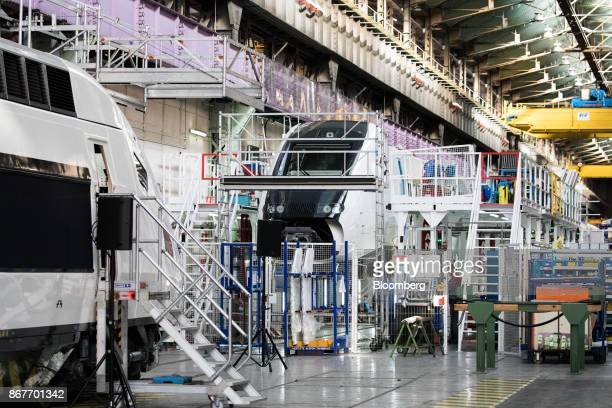 A pair of TGV railway trains stand under assembly on the production line inside the Alstom SA highspeed train factory in Belfort France on Thursday...
