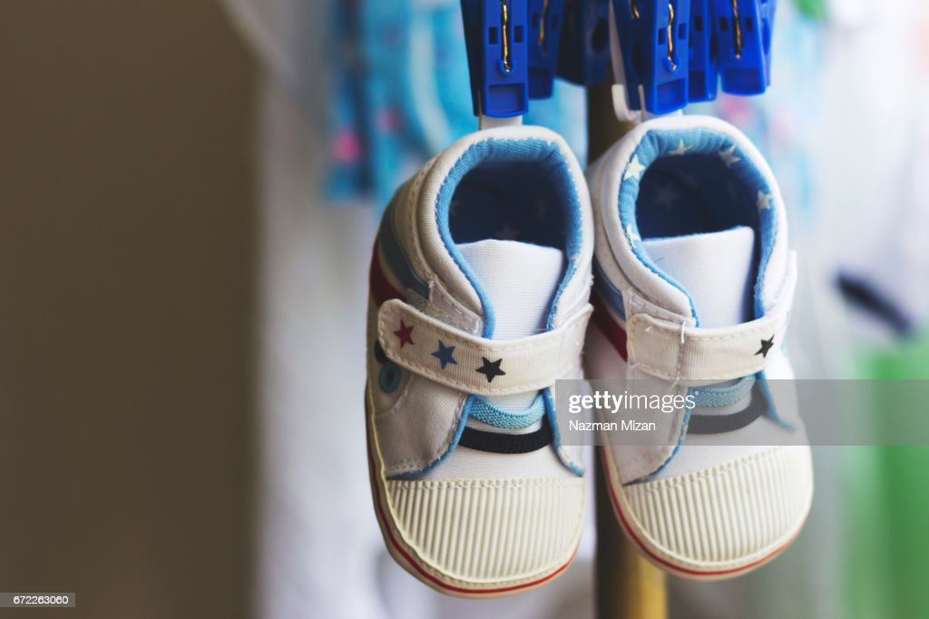 A pair of tiny shoes hanging on clotheslines. : Foto de stock
