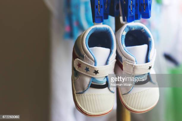 a pair of tiny shoes hanging on clotheslines. - baby booties stock photos and pictures
