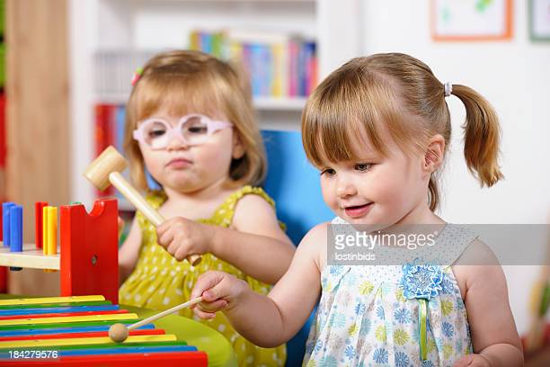 Pair Of Toddlers Enjoying Music/ Playtime In A Nursery Setting
