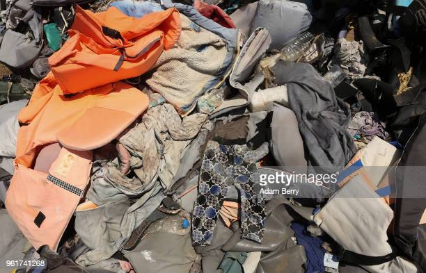 A pair of toddler's pants lays among thousands of used life preservers and pieces of rafts used by refugees in their attempted crossings from Turkey...