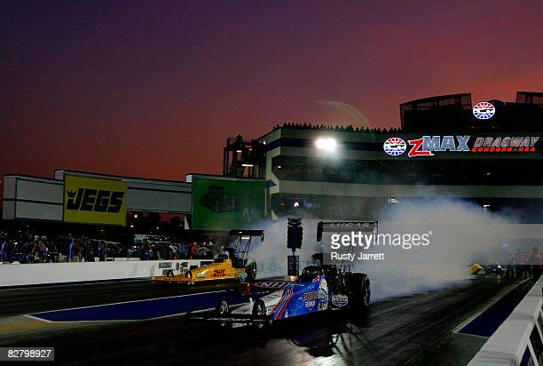 A pair of top fuel dragsters burn out at twilight during second round qualifying for the NHRA Carolinas Nationals at the Zmax Dragway on September 12...