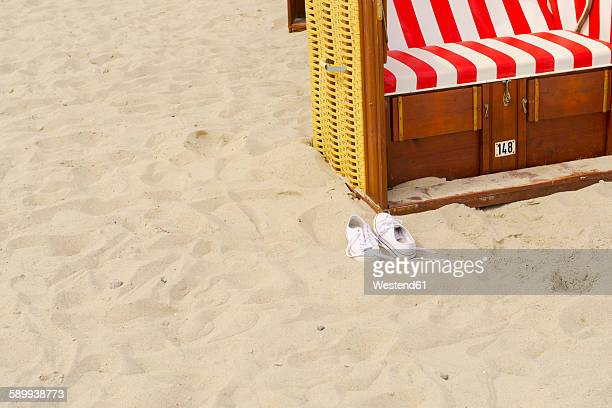 Pair of trainers and hooded beach chair on the beach