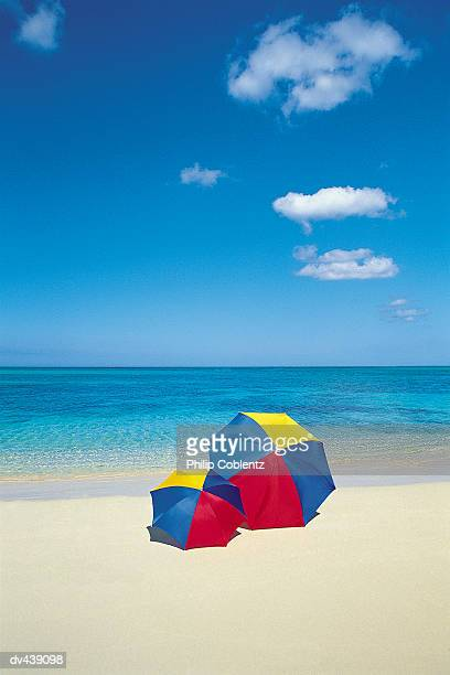 pair of umbrellas on tropical beach - side by side stock pictures, royalty-free photos & images