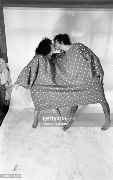 A pair of unidentified model kiss while dressed in a twoperson polka dot outfit at a 'nude fashion' event New York New York July 30 1969