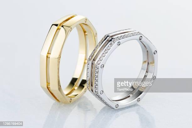 pair of unique wedding rings with diamonds on white background - ホワイトゴールド ストックフォトと画像