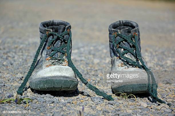 Pair of used work boots on road, close up