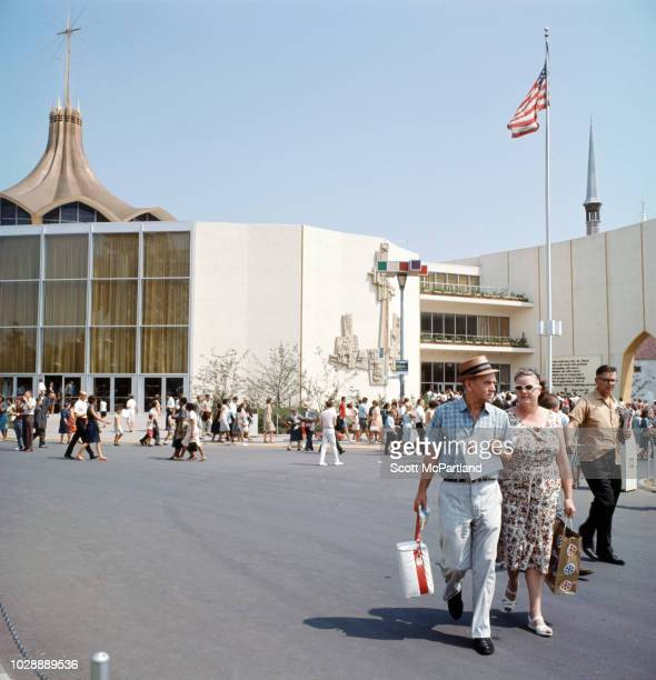 A pair of visitors among others walk near the Vatican Pavilion at the World's Fair in Flushing Meadows Park in Queens New York New York June 1965