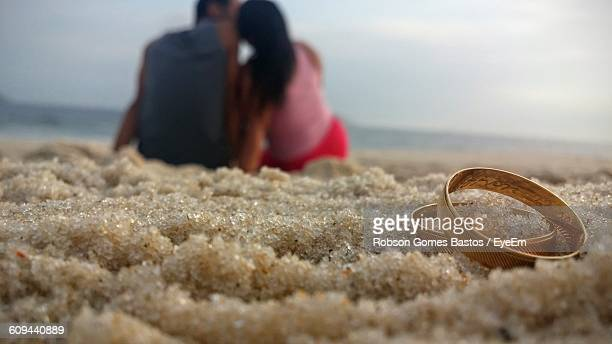 Pair Of Wedding Rings On Sand With Couple Sitting In Background