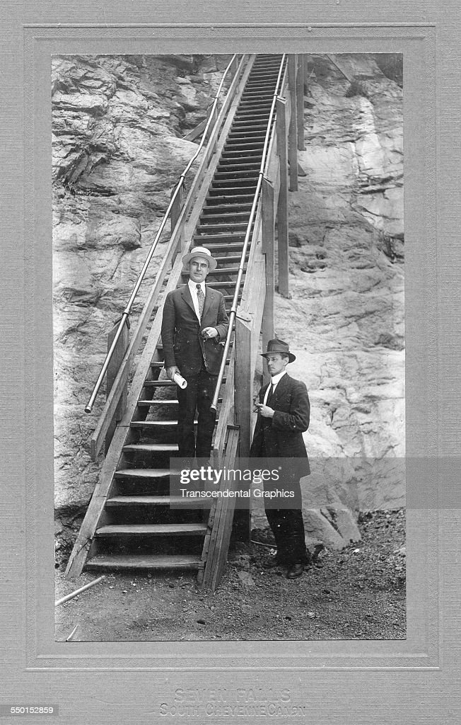 A Pair Of Western Tourist Pose By The Stairs Which Climb Besides Seven  Falls, Colorado