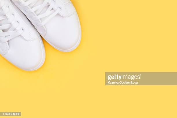 pair of white shoes on yellow background. trendy summer color, monochrome image with copy space. hipster concept. - yellow shoe stock pictures, royalty-free photos & images