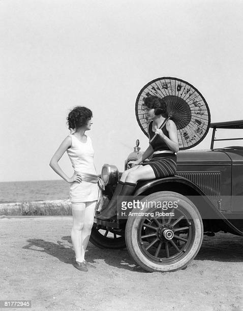 pair of women in old fashioned bathing suits at beach one sitting on car with oriental umbrella other standing in front of car talking to her. - 1920 car stock photos and pictures
