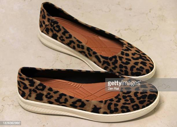 a pair of women's casual slip-on leopard print shoes - brown shoe stock pictures, royalty-free photos & images