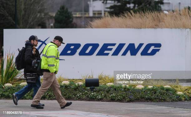 A pair of works walk in to the Boeing 737 factory on December 16 2019 in Renton Washington The company announced it is suspending production of the...