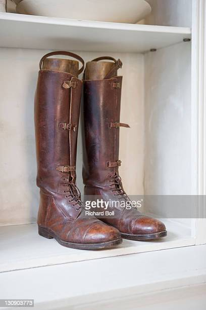 A pair of worn leather riding boots on a shelf.