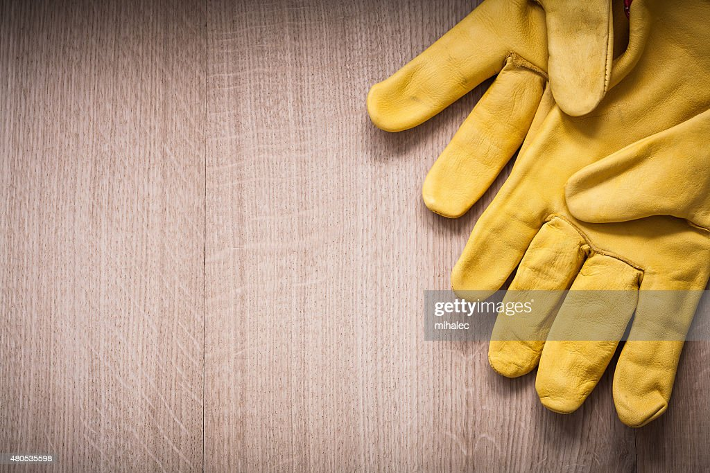 Pair of yellow leather safety gloves on wooden board copy : Stockfoto