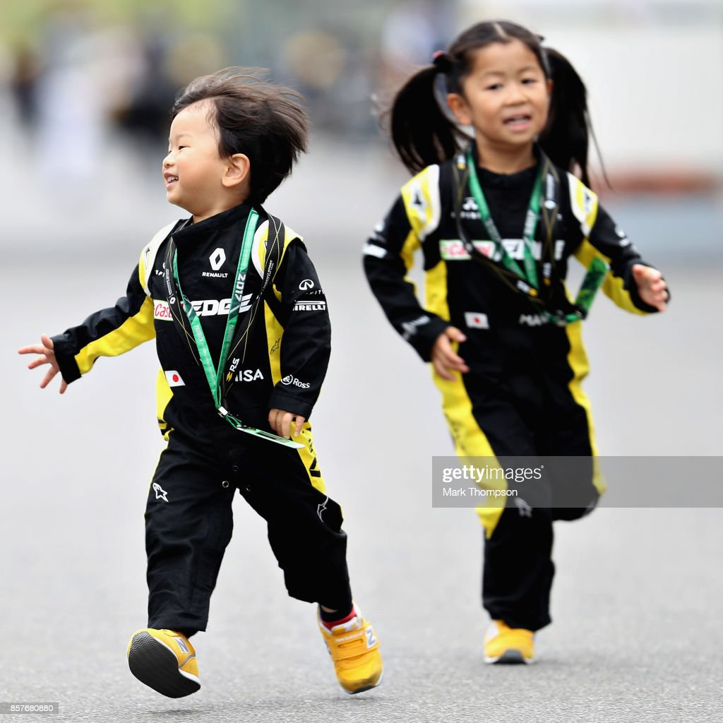 A pair of young fans run around in the Paddock during previews ahead of the Formula One Grand Prix of Japan at Suzuka Circuit on October 5, 2017 in Suzuka.