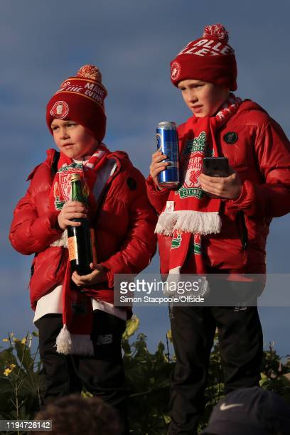 A pair of young Liverpool fans hold bottles and cans of alcohol as they stand on a wall before the Premier League match between Liverpool FC and...