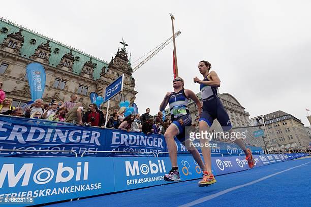 Pair with a blind female athlete of the paratriathlon runs to the finish line at ITU World Triathlon Hamburg on July 16, 2016 in Hamburg, Germany.