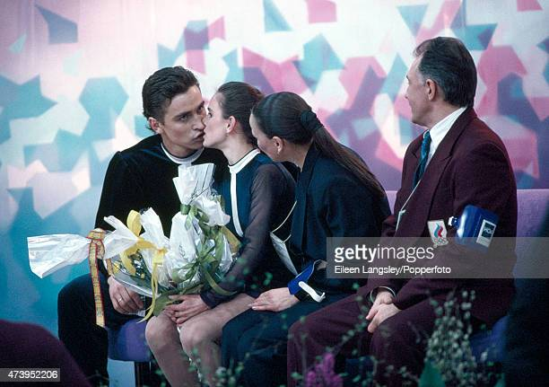 Pairs figure skaters Sergei Grinkov and Ekaterina Gordeeva of the USSR with their coaches await the results of their performance at the Winter...
