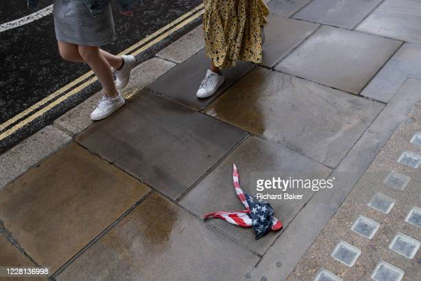Pairs of legs walk past an American Stars and Stripes flag bandana lies on the wet pavement in the City of London, the UK capital's financial...