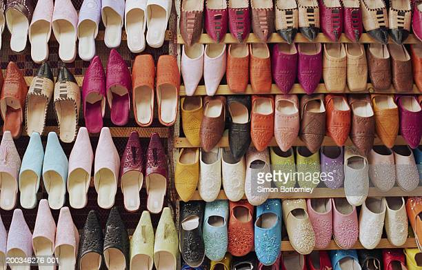 Pairs of multicoloured shoes on rack, full frame