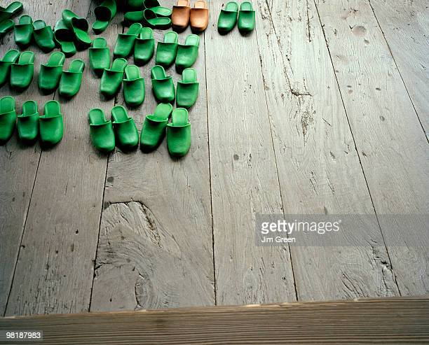 Pairs of slippers on a wooden floor