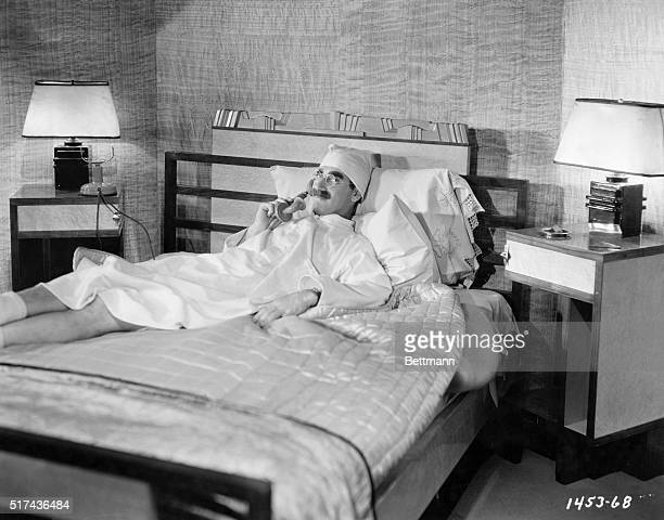 Pajamaclad comedian Groucho Marx lying on a bed while talking on the phone in a publicity shot for the 1933 film Duck Soup